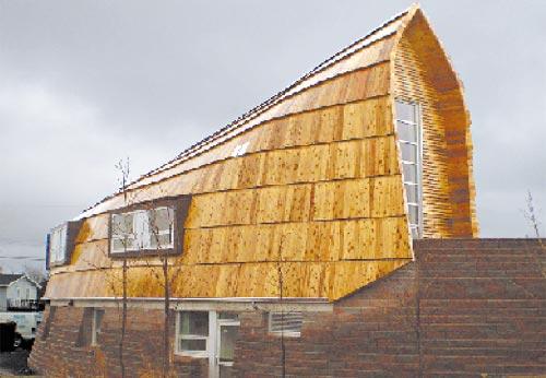 Manto. La cubierta de madera de pícea cae como una capa sobre el basamento.