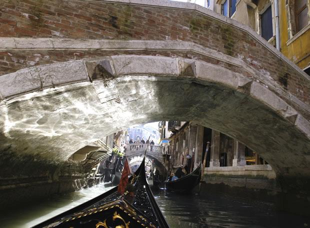 Góndolas navegando bajo los puentes de los canales de Venecia