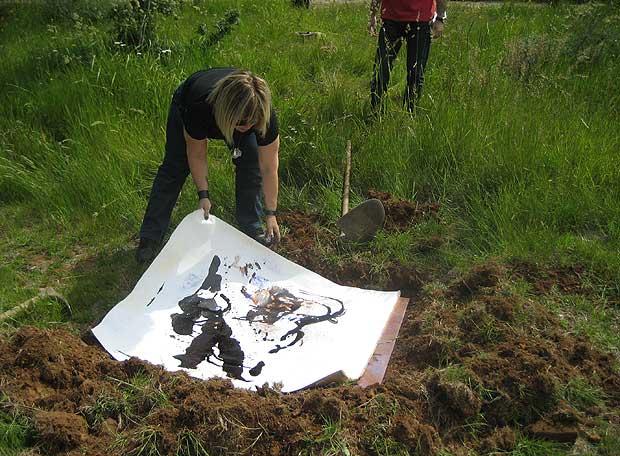 Christina Oiticica enterrando uno de sus lienzos