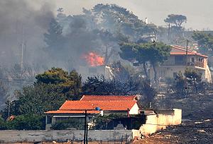 Dos casas 'asoman' entre la vegetación en llamas en los montes cercanos a Atenas   Afp