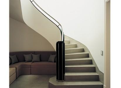Escalera con torre facetada de mármol negro, baranda cromada. Para el rincón que deja libre, se encargó un sillón a medida (Monica Maestri)