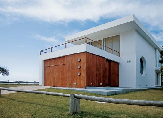Sobre el garaje con puertas de pino tea (material que recubre la planta baja hasta llegar al acceso principal), una terraza para mirar las olas desde el living