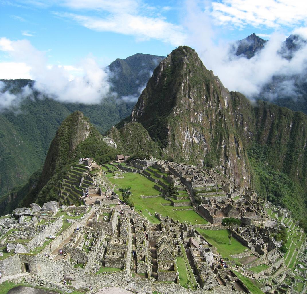 Vista de sur a norte. A la izquierda se ve el sector Hanan de la ciudad (con la estructura piramidal de la colina del Intihuatana) y a la derecha el sector Oriente, separadas por la plaza principal. Al fondo el Cerro Huayna Picchu. La imagen está tomada desde lo alto del sector agrícola, al sur del complejo. Wikipedia.