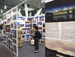 Varias personas observan el mural de fotografías y diseños instalados en el Congres de Arquitectura. EFE